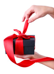 Woman's hand holding ribbon and opening gift box isolated