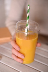 Female hand at wooden table with fast food closed cup of orange