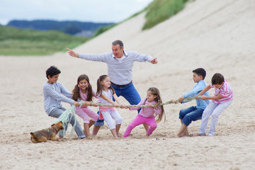 Grandfather supervising grandchildren playing tug-of-war on beach