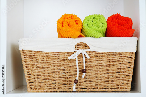 Colorful towels with wicker basket on shelf of rack background - 78527884