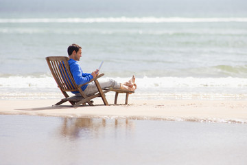 Man using digital tablet in deck chair on beach
