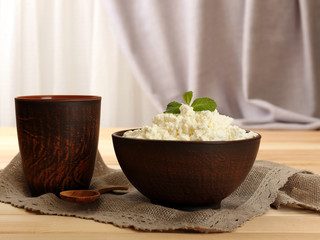Cottage cheese in bowl with cup on table on fabric background