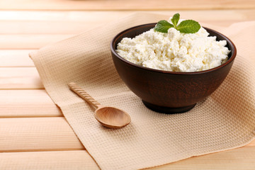 Cottage cheese in bowl with spoon on napkin on wooden
