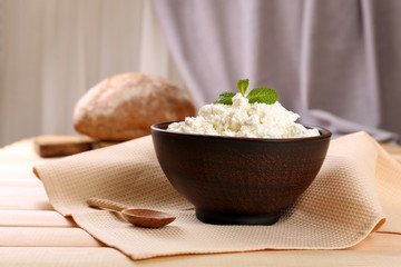 Cottage cheese in bowl with bread on table on fabric background