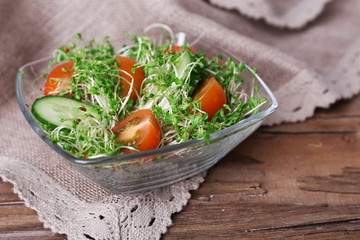 Cress salad with sliced cucumber and cherry tomatoes in glass