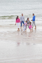 Multi-generation family playing together on beach
