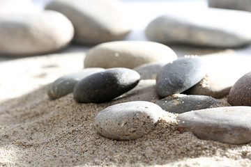 Gray sea pebbles on sand background