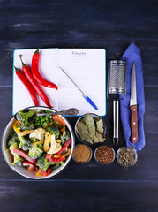 Frozen vegetables and blank notebook, on wooden table