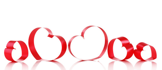 Red ribbons in shape of hearts isolated on white