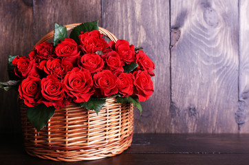 Bouquet of red roses in basket on wooden background