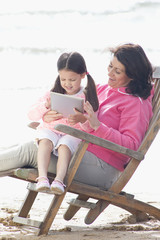 Grandmother and granddaughter using digital tablet in deck chair on beach