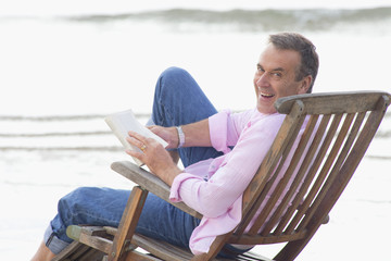 Older man reading book in deck chair on beach