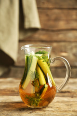 Glass ewer with fresh organic cucumber water on wooden table