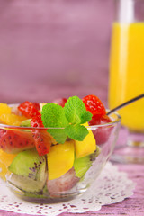 Fruit salad with mint and orange juice in glassware