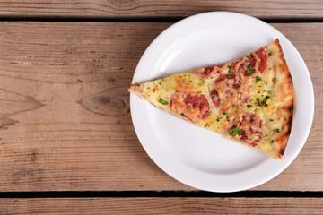 Tasty slice of pizza on plate on wooden table