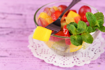 Fruit salad with mint in glassware on color wooden background