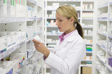 Pharmacist reading prescription and bottle in pharmacy