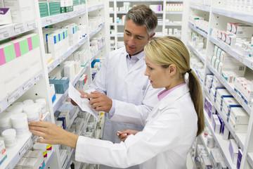 Pharmacists searching for medication on pharmacy shelves