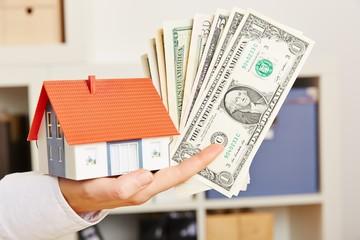 Hand mit Dollar und Haus