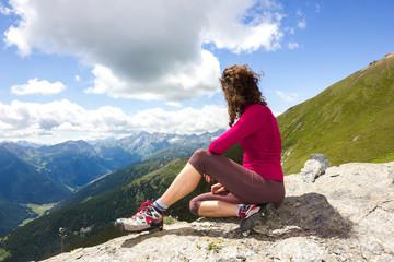 Giovane ragazza seduta ammira paesaggio di montagna