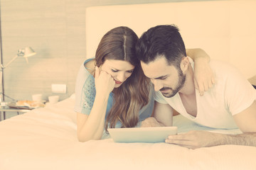 Young Couple with Digital Tablet on Bed.