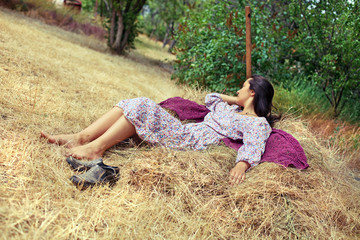 Young woman resting on a haystack