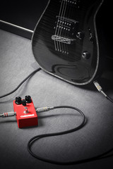 Guitar conneted to red overdrive effect pedal
