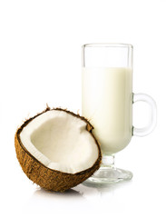 half of fresh coconut and coconut milk in a glass