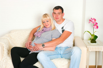 Young pregnant couple sitting on a sofa in a room
