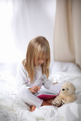 Little girl lying in bed and reading a book