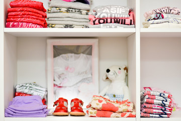 Baby clothes and shoes placed on wooden shelves white