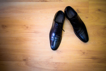 Black shoes groom sitting on hardwood floors
