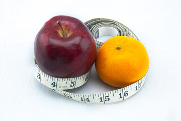 Red Apple and Orange with Measure Tape on White Background