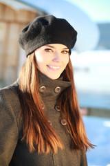 Jeune femme souriante devant un chalet l'hiver