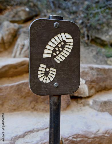 Plexiglas Alpinisme Hiking boot sign on trail