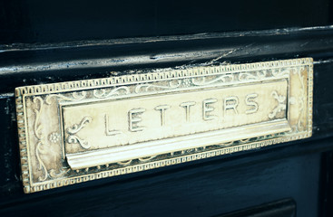 Brass letterbox slot  in old door, toned
