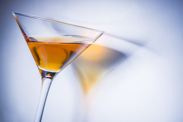 Orange liqueur into a martini glass.