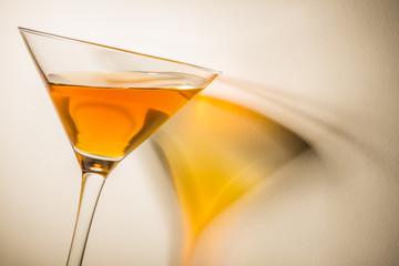 Orange liqueur into a martini glass.