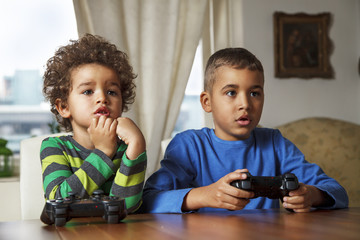 Afro American boys playing video games at home.