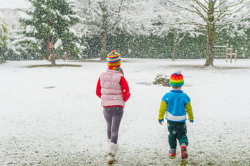 Kids in colorful clothes walking in a park under snowfall