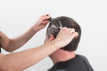 Hairdresser trimming man's brown hair with scissors
