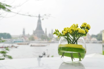 Yellow flowers in a short glass vase with river and temple backg