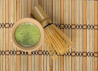 Green tea in clay cup with bamboo whisk