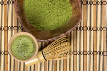 Green tea in cup with bamboo whisk