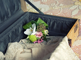 Open vintage suitcase with lace dress and small bouquet