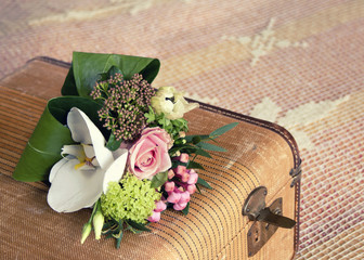 Small bouquet of flowers on vintage suitcase; vintage filter