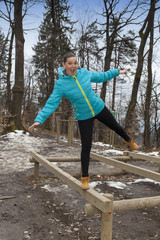 Pretty sporty girl working out on balance beam