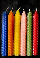 Full natural beeswax candles on black background
