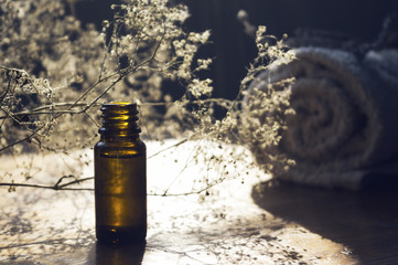 Essence bottle and small white flowers and towel on wooden table