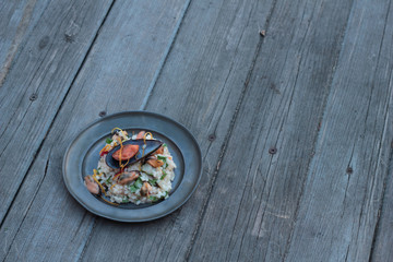 Risotto with seafood, chili and parsley on a tin plate.